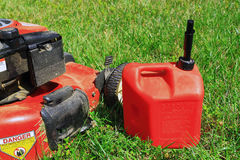 Gas Lawn Mower. With red gas can on green grass field stock image