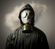 Gas mask and cloud. Man wearing a gas mask on his face and a cloud behind his back Stock Images
