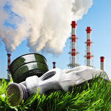 Gas mask on a green grass on a background of smoking chimneys Royalty Free Stock Photography