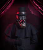 Gas Mask Magician. A Magician, wearing modded gas mask and a top hat, standing against red background, under red curtains Royalty Free Stock Images