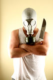Gas Mask Man with Knife. A mean looking man wearing a gas mask and holding a knife Royalty Free Stock Photo