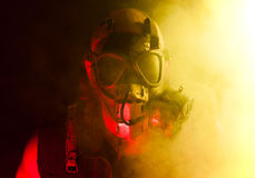 Gas mask punk. A creepy guy with post apocalyptic vibes wearing a gasmask in a smoke or fog cloud that's colored bright yellow while being lit with a red Stock Photos
