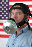 Gas Mask Vertical. A man wearing a gas mask and standing in front of an American flag royalty free stock photos