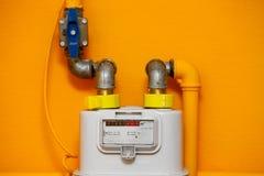 Gas meter. On orange wall stock image