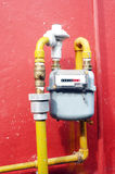 Gas meter. On the red wall Stock Photos