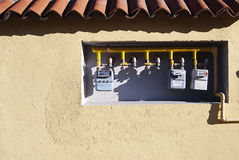 Gas meters. Three gas meters inside ocher wall in old building Stock Image