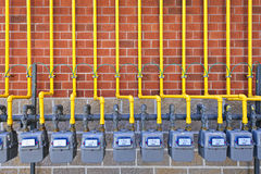 Gas meters on brick wall. Row of natural gas meters with yellow pipes on building brick wall Royalty Free Stock Photos