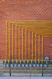 Gas meters on brick wall. Row of natural gas meters with yellow pipes on building brick wall Stock Photography