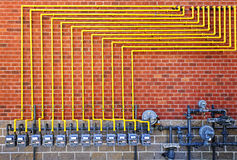 Gas meters on brick wall. Row of natural gas meters with yellow pipes on building brick wall Royalty Free Stock Images