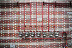 Gas meters and pipe on brick wall. Row of residential natural gas meters and pipe on brick wall Royalty Free Stock Photos