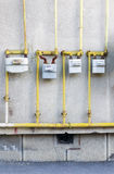 Gas Meters. Vintage row of residential natural gas meters and yellow pipes plumbing on exterior wall to measure household energy consumption Stock Photo