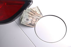 Gas money. One hundred dollars ($100) USD worth of twenty dollar bills sticking out of a car gas tank cover royalty free stock photos