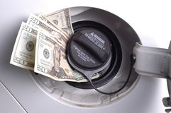 Gas money. One hundred dollars ($100) USD worth of twenty dollar bills sticking out of a car gas cap royalty free stock photography