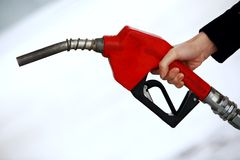 Gas nozzle in woman's hand Royalty Free Stock Photo