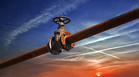 Gas/oil pipe line with valve. Gas/oil old rusty pipe line against sky sunset background royalty free stock image