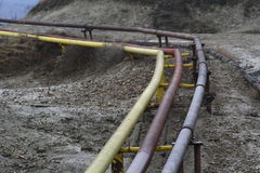 Gas and oil pipes. Yellow gas and oil pipes for transport on field in a deserted polluted area Royalty Free Stock Photo