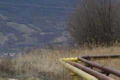 Gas and oil pipes. Yellow gas and oil pipes for transport on field in a deserted polluted area Royalty Free Stock Photography