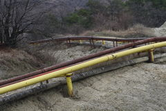 Gas and oil pipes. Yellow gas and oil pipes for transport on field in a deserted polluted area Royalty Free Stock Photos