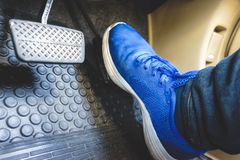 The gas pedal brake pedal. On the blue shoes Royalty Free Stock Photo