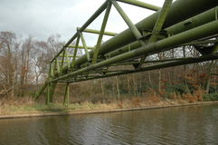 Gas pipeline over a canal. A green gas pipe links over a canal in the north of England, UK Royalty Free Stock Photos