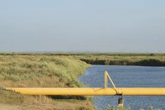The gas pipeline through the small river. Equipment of oil and gas crafts stock images