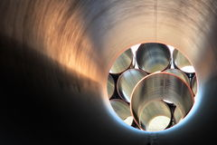 Gas pipes in striking pattern. Lines of 2m diameter gas storage pipes piled up ready for laying. Brushed metallic surface provides fantastic uplighting. Can be Royalty Free Stock Images