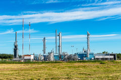 Gas plant. In countryside surrounded by farm fields. Background of blue sky, white clouds Stock Photos