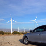 Fossil Fuel Powered Car vs Clean Wind Energy Stock Photo