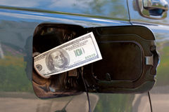 Gas Prices. Banknote of 100 dollars is in petrol tank Stock Images