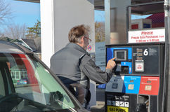 At The Gas Pump. A senior vehicle onwer using the pay-at-the-pump interface at a sef serve gas station Royalty Free Stock Photos