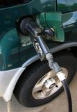 At the Gas Pump. A gas pump nozzle refueling a green car Stock Photo