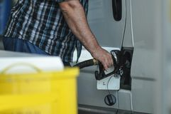 Gas pump. Close-up of a men hand refilling the car with a gas pump stock image