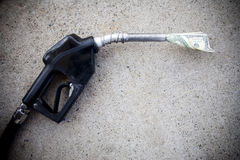 Gas pump with money in the nozzle. Close up of gas pump with money in the nozzle royalty free stock images