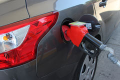 Gas Pump Nozzle in Car. A gas pump nozzle shown inserted in the gas door of a north american automobile to fill it with gasoline Stock Image