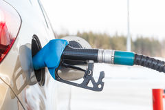 Gas pump nozzle in fuel tank of a new car Royalty Free Stock Images