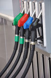 Gas pumps. Row of gas pumps with different color handles indicating the different grades of gas Stock Image