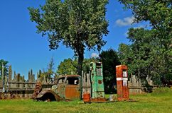Gas Pumps and Junked Pickup. Several gas pumps, cans, and the body of an junked pickup are left at the edge of a woods Stock Images
