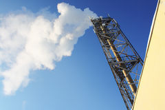 Gas. Smoke leaving a pipe. On blue sky Royalty Free Stock Photography