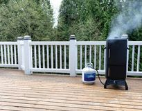 Smoker with fresh smoke coming out of BBQ cooker on outdoor deck. Gas smoker on cedar outdoor deck with woods in background royalty free stock image