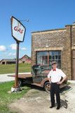 Vintage Gas Station, Attendant, Nostalgia. Gas station attendant at an old, retro filling station. A vintage antique truck is in the background along with a farm royalty free stock photos