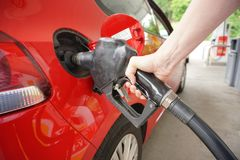 Woman`s hand pumps gas into car royalty free stock image