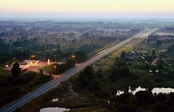 A gas station and a direct highway at dusk. View from above. Gas station and empty highway at dusk. View from above stock image