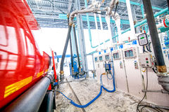 Gas station at oil refinery factory tank filling. Gas station for trucks at oil refinery factory tank filling on truck Stock Images