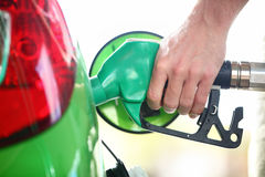 Gas station pump - filling gasoline in green car. Gas station pump. Man filling gasoline fuel in green car holding nozzle. Close up Stock Photos