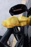 Gas Station Pump Nozzle in Car Tank Filling Intake. Gas station pump nozzle inserted into a car fuel tank intake to fill up the vehicle with premium unleaded Stock Images