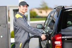Gas station worker refilling car at service station Stock Photos
