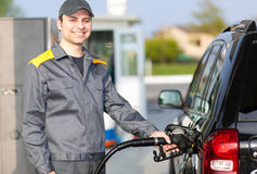 Gas station worker refilling car at service station Royalty Free Stock Photo