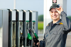 Gas station worker refilling car at service station Stock Images