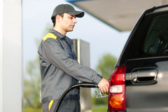 Gas station worker refilling car at service station Royalty Free Stock Photography