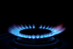 Gas stove. Blue flames of gas stove in the dark Stock Photos